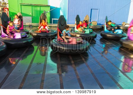 Los Angeles CA USA - July 6 2013: Children having fun in bumper cars in Pacific Park at Santa Monica peer. Motion blur technique.