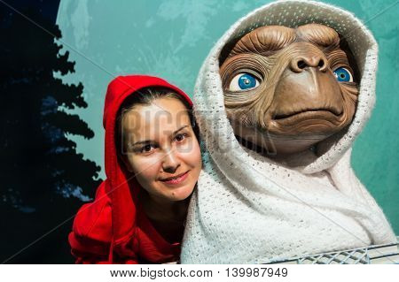 Los Angeles CA USA - July 6 2013: Female tourist being photographed near E.T. science fiction character in Madame Tussaud's Hollywood exhibition.