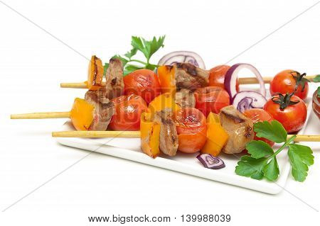 skewers of meat with vegetables on a plate close-up. white background - horizontal photo.