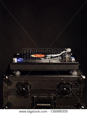 professional dj turntable on flight case, dark background