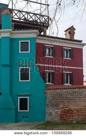 Colorful buildings and brick fence in Burano Italy an island with colorful architecture in the Venetian Lagoon.