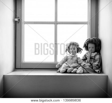 Two dolls near the window. Black and white photo.
