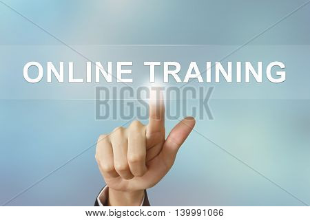 business hand pushing online training button on blurred background