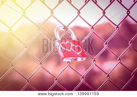 Two hearts on Love Lockers on the fence with pink tone and soft light style