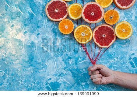 Orange tangerine and grapefruit in conjunction as balloons the hand holding the strings.