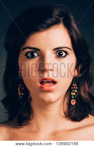 Portrait of a young shocked woman having mouth opened - isolated on black.
