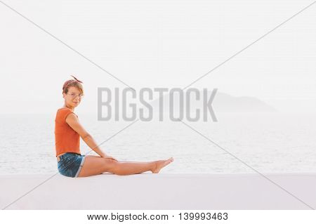 Young woman sitting on the white wall by the sea