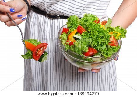 Healthy food and diet concept. Woman's hands holding fresh vegetable salad meal with fork in hand isolated on white background. Modern dieting and weight loss nutrition