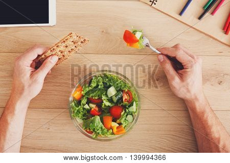 Business lunch at working place. Businessman in office. Hands of eating man closeup. Healthy, diet food, vegetable salad with apple and juice. Notebook, tablet and pencils. Top view, flat lay