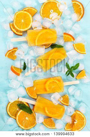 Fruit Orange Ice Lolly On Light Blue Background.