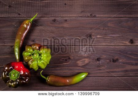 Multicolor paprika with chilli peppers on wooden background