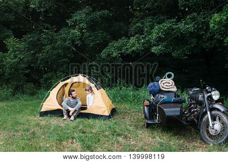 Family camping, dad with daughter and motorcycle with sidecar in forest, free space, Travel photo of happy family weekend