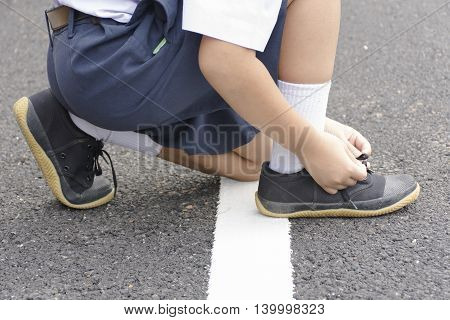 Childs student  tying shoes at roadside.Background child going to school.