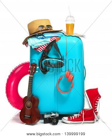 The blue suitcase, sneakers, hat and rubber ring on white background. The travel, tourism and holidays concept