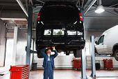 Minibus service maintenance, professional garage interior, lifted car on elevator poster