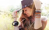 Fashion smiling woman portrait with hat on a head, sunny backlit outdoor photo, boho chic style, hipster style poster