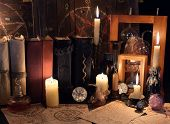 Witch table with magic objects, burning candles and old mystic parchments. Halloween concept, scary ritual or spell with occult and esoteric symbols poster