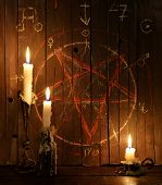Three burning candles against the background of wooden planks with bloody pentagram. Halloween concept, black magic ritual or satanic spell with occult and esoteric symbols poster