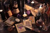 Still life with the tarot cards, knife, book, magic objects and evil candles on witch table. Halloween concept, black magic ritual or spell with occult and esoteric symbols, divination rite poster
