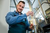 Happy brewer checking beer with hydrometer at brewery poster