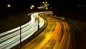 Highway traffic at night - long time exposure was used to show car movements. poster