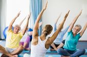 Instructor performing yoga with seniors during sports class poster