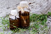 Medicinal plant shepherd's purse (Capsella bursa-pastoris) and brown pharmaceutical bottle on old wooden table. Used in herbal medicine healthy eating as well as for cosmetics purposes poster