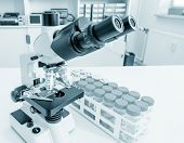 Water sampling procedure for microbiological analysis. Science microscope on lab bench. Microbiology laboratory. Blue toned image of binocular microscope.  poster