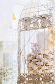 An artificial cake in a white cage. poster