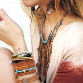 Female neck and hands with many boho bracelets, leather necklace and earrings with feathers, turquoise and brown, outdoor fashion photo poster