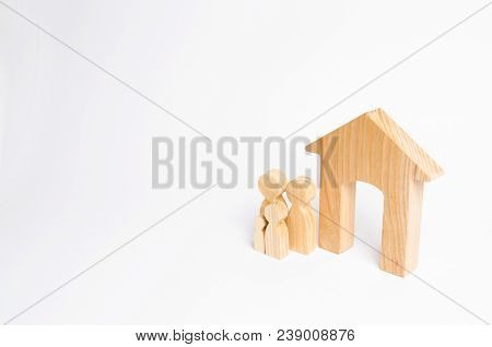 A Young Family With Children Is Standing Near A Wooden House. The Concept Of A Strong Family, The Co