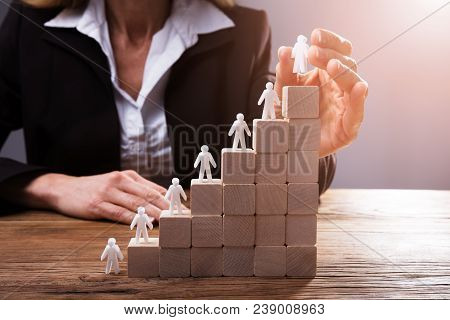 Businessperson Placing Human Figures On Staircase