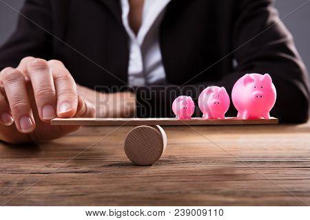 Businessperson's Finger Balancing Piggybanks On Seesaw