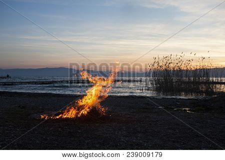 Sunset On A Beach By The Lake Ohrid Near Struga. Flame And Smoke From Burning Of A Cut Reeds. Fire R