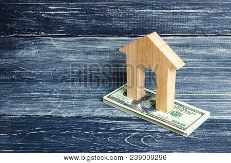 A Wooden House Stands On A Stack Of Dolor Banknotes. The Concept Of Buying And Selling Immovability,