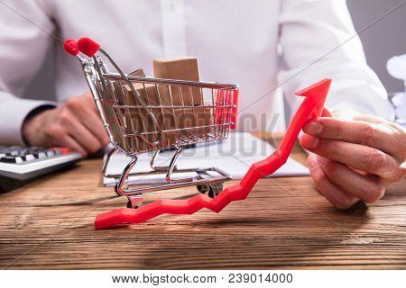 Businessperson Holding Arrow Showing Upward Direction