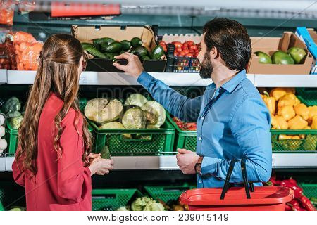 Back View Of Couple With Shopping Basket Shopping Together In Supermarket