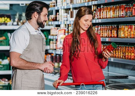 Portrait Of Shop Assistant In Apron And Female Shopper In Hypermarket