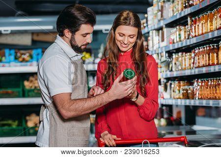 Portrait Of Shop Assistant In Apron Helping Female Shopper In Hypermarket