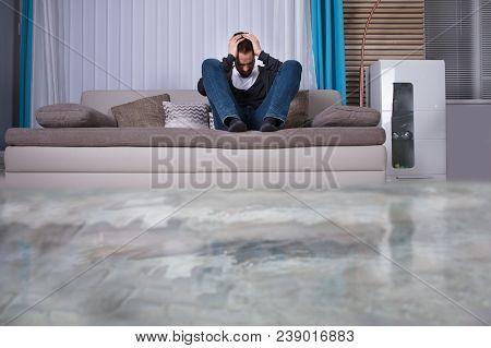 Upset  Man On Sofa With Hands On Head In Room Flooded With Water