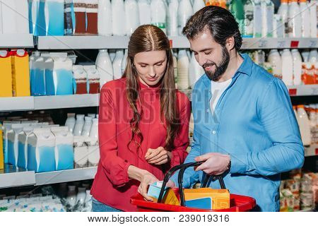 Portrait Of Couple With Shopping Basket Shopping Together In Supermarket