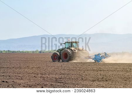 Farmer In Tractor Preparing Land Seedbed Cultivator. Agriculture Tractor Landscape.