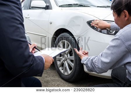 Man Agent Filling Insurance Form Near Damaged And Examining Car, Traffic Accident And Insurance Conc