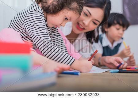 Cute Kids And Asian Teacher Drawing In Artist Class. Back To School And Education Concept. Nursery A
