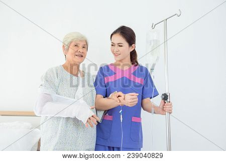 Beautiful Asian Nurse Helping Senior Patient To Walking