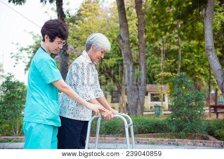 Asian Nurse Helping Senior Female Patient Walking By Walker Support