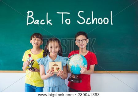 Three Asian Student Smiling In Front Of Chalkboard With Text
