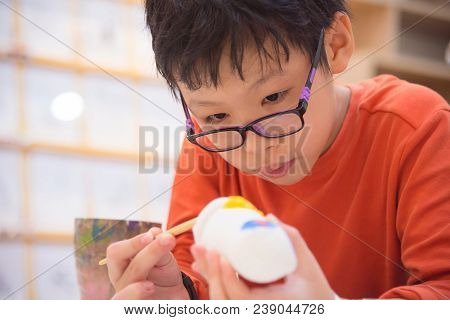 Young Asian Boy Painting Craft By Color Brush In Classroom At School