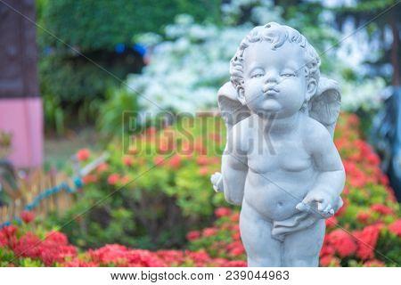 Cupid Stone Statue In The Flower Garden.