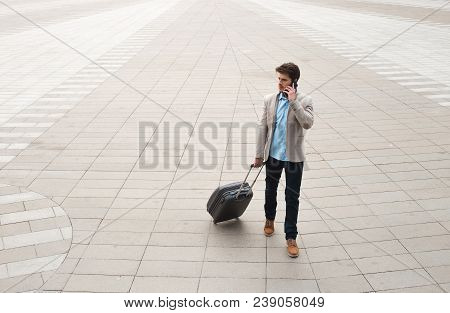 Travel Abroad For Business! Awesome Young Entrepreneur Holding A Mobile Phone And Standing With Bagg